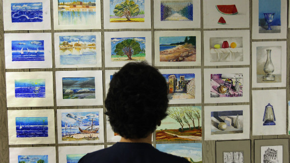 A camp librarian views artwork painted by detainees in September 2010.