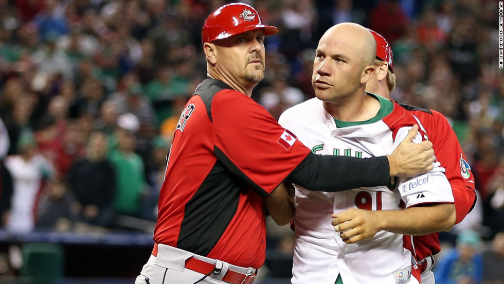 Pitcher Alfredo Aceves of Mexico is held back by coach Larry Walker of Canada during an on-field altercation between both teams in the World Baseball Classic on Saturday, March 9.