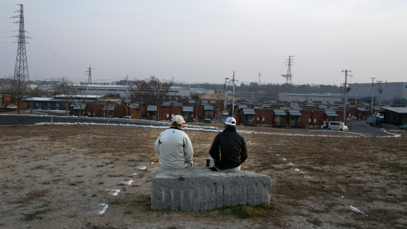 Men sit on a bench in front of a temporary housing shelter on Thursday, March 7, in Motomiya, Fukushima Prefecture. Thousands were displaced in the aftermath of the earthquake.