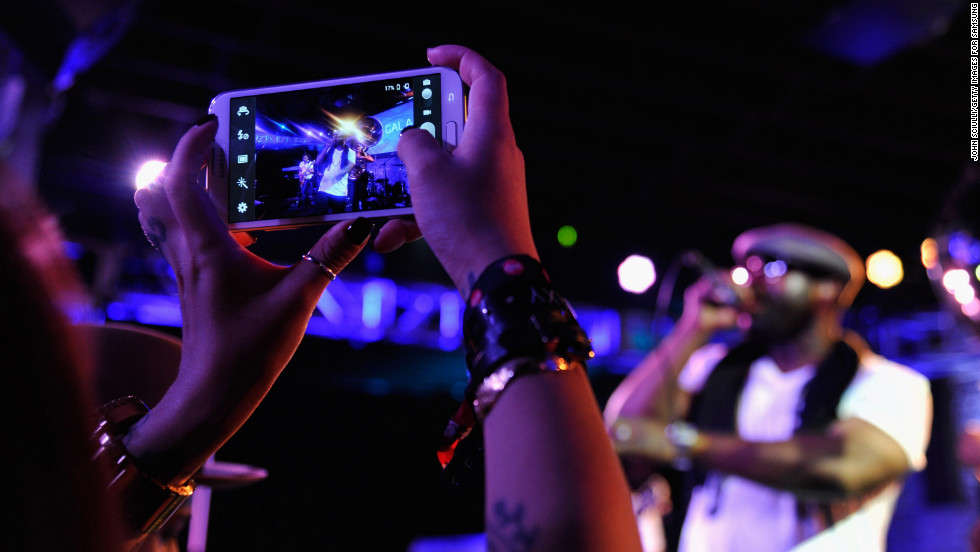 An attendee uses her mobile phone to snap a picture of The Roots' show on March 9.