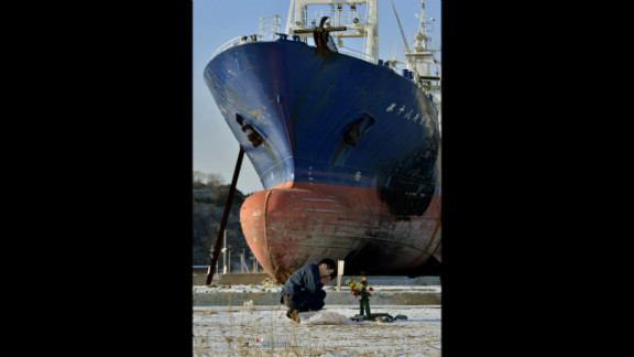 A man mourns on Monday in front of a ship brought ashore by the 2011 tsunami in Kesennuma, Japan.