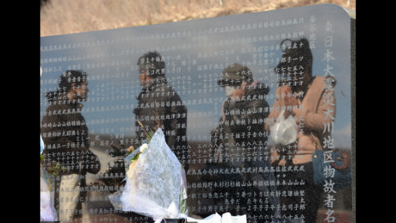 People visit a memorial altar at the Okawa elementary school where at least 70 students died in the 2011 tsunami, in Ishinomaki, Japan, on Monday.