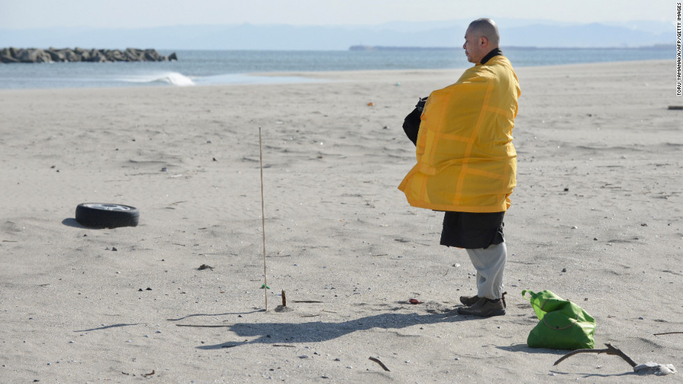 A Buddhist monk prays for tsunami victims at Arahama district in Sendai, Japan, on Monday.