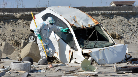 A police officer searches for remains in a wrecked vehicle at a beach in Namie, Japan, near the stricken Fukushima Dai-ichi nuclear plant, on Monday, March 11, the second anniversary of the tsunami. Two years ago, a magnitude-9.0 earthquake unleashed a wall of water that killed nearly 16,000 people in northeast Japan and sparked the world's worst nuclear crisis in 25 years.