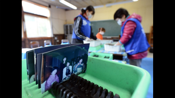 Volunteers clean pictures found in debris from the earthquake and tsunami disasters at the Tsukidate elementary school in Kesennuma, Japan, on Sunday, March 10.