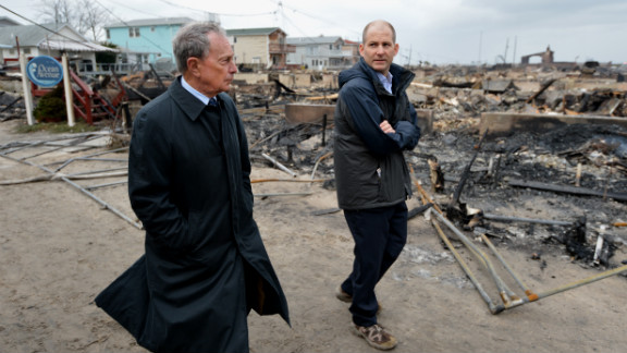 In October 2012, Bloomberg views damage in the Breezy Point area of Queens, where a fire destroyed about 80 homes as a result of Hurricane Sandy. Sandy killed at least 113 people in the United States and heavily damaged New York's infrastructure.