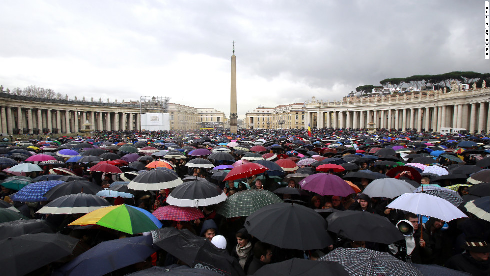 People shelter under umbrellas while they wait in St. Peter's Square for news on the election of a new pope on March 13 in Vatican City.