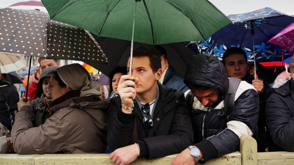 People wait under umbrellas for the College of Cardinals to elect a new pope.