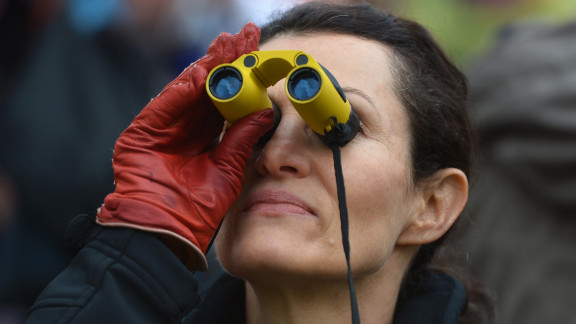 A woman looks to the chimney of the Sistine Chapel on St. Peter's Square, waiting for the smoke on March 13.