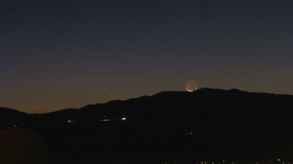 """Brian Karczewski, 24, captured the comet alongside the crescent moon overlooking the Ortega Mountains in California. """"I love astronomy and find astrophotography a good challenge,"""" he said. """"I was very excited to capture the comet next to the moon. Never photographed a comet before!"""""""