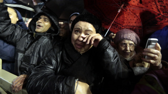 A woman in the crowd wipes away tears.