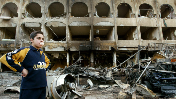 A boy stands at the scene of a car bombing in front of the Shaheen Hotel in Baghdad on January 28, 2004.