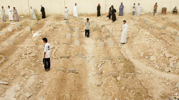 Iraqis look at rows of graves at an overflowing cemetery built in a soccer arena in Fallujah on May 3, 2004.