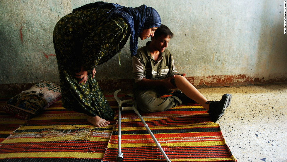 At home in Baghdad with his new prosthetic leg, Ahsan Hameed, 20, sits while his aunt looks it over on July 17, 2004. He lost his left leg above the knee to a stray bullet in April.