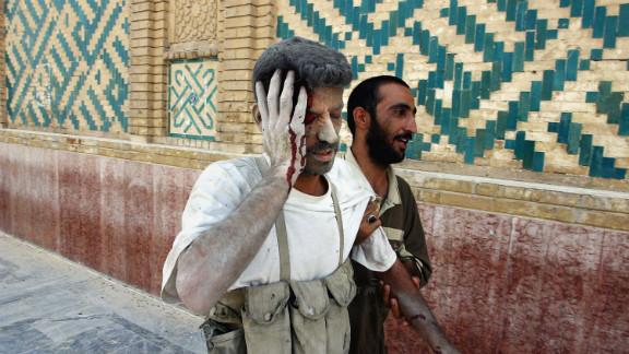 An Iraqi militia member injured in a U.S. airstrike in Najaf is assisted by one of his comrades on August 24, 2004. They were walking past the shrine of Imam Ali to make their way to a militia hospital.