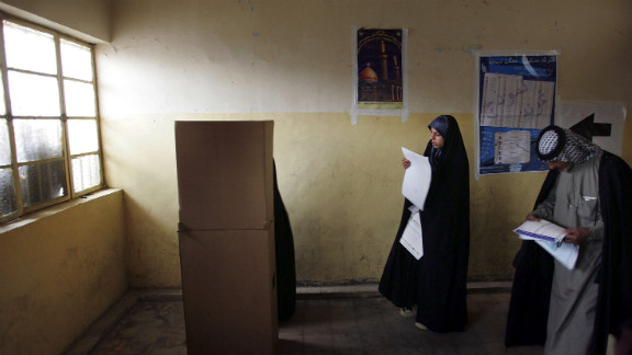 Iraqis look over their ballots on election day in the Sadr City neighborhood of Baghdad on January 30, 2005. It was the country