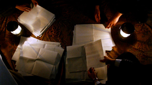 Election officials count ballot papers at night on January 30, 2005, in the Shiite holy city of Najaf. Despite threats, thousands of men and women cast their votes.