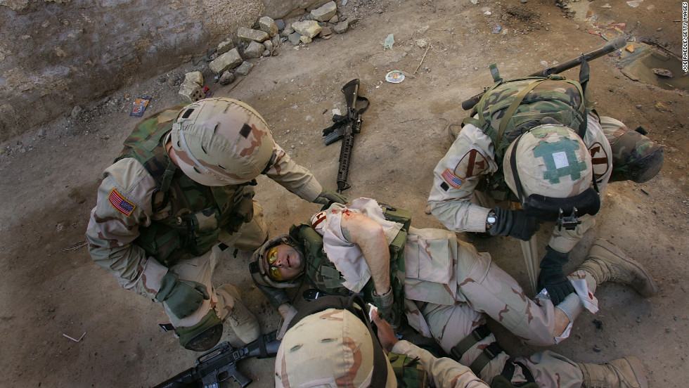 Army Sgt. 1st Class Troy Hawkins is tended to after getting wounded during a firefight while on patrol with an Iraqi army unit in the Haifa Street neighborhood of Baghdad on February 16, 2005. Afterward, he continued to fight in the narrow streets.