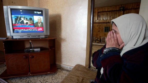 A Palestinian woman watches the news of Saddam Hussein