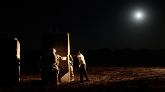 U.S. soldiers and an Iraqi contractor build a concrete wall between Sunni and Shiite areas of the south Dora neighborhood of Bagdhad in the early hours of July 4, 2007.