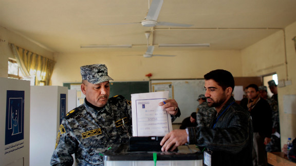 A poll worker helps a member of the Iraqi National Police cast his ballot in Baghdad on January 28, 2009. Polls were opened early to members of the Iraqi security services, many of whom would be working during the provincial elections.
