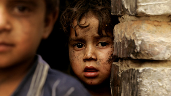 A boy looks out from his family shelter at a Narwan brick factory on July 1, 2008.