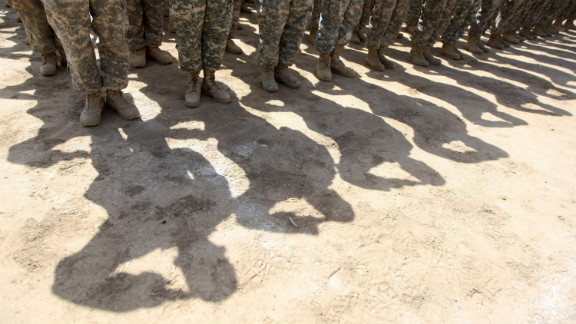 U.S. soldiers salute during a handover ceremony of the entry points of Baghdad