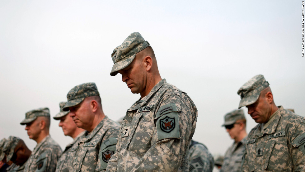 Military personnel lower their heads during the flag casing ceremony in Baghdad on December 15, 2011. The ceremony officially marked the end of U.S. military operations in Iraq.