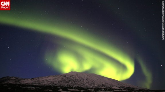 """A spectacular solar event over the weekend provided a stunning showing of the northern lights, or aurora borealis. This image by Stefan Ingvar Gudmundsson from Iceland captures the lights <a href=""""http://ireport.cnn.com/docs/DOC-943369"""">appearing to curl</a> around the Snaefellsjokull glacier."""