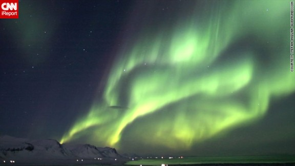 """The lights of the Icelandic village of Olafsvik <a href=""""http://ireport.cnn.com/docs/DOC-943369"""">are dwarfed </a>by the northern lights in another image from Gudmundsson."""