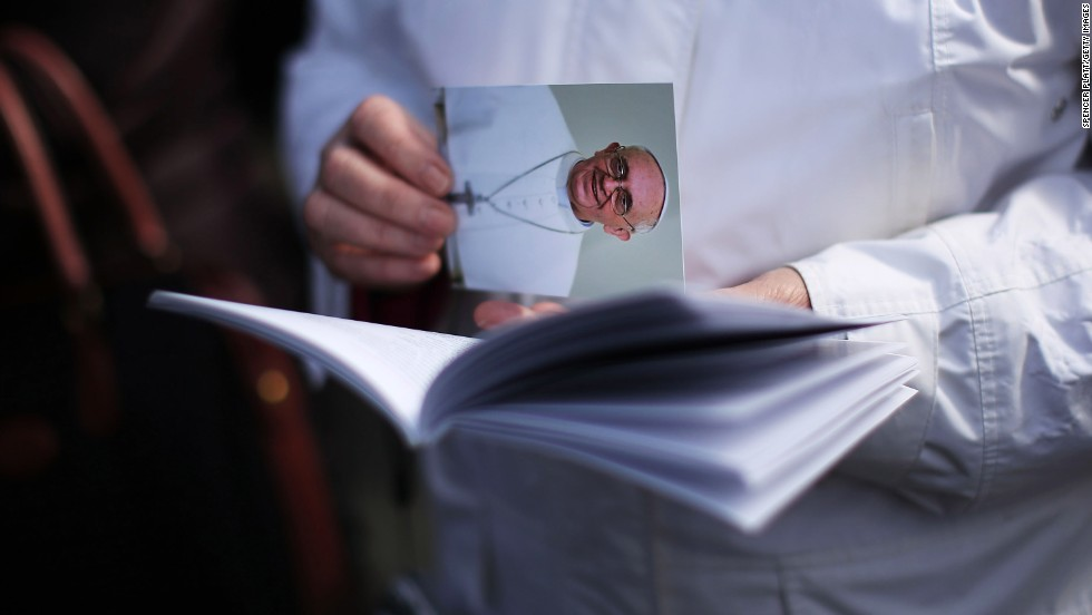 A woman holds a card with Francis' picture during the Mass.