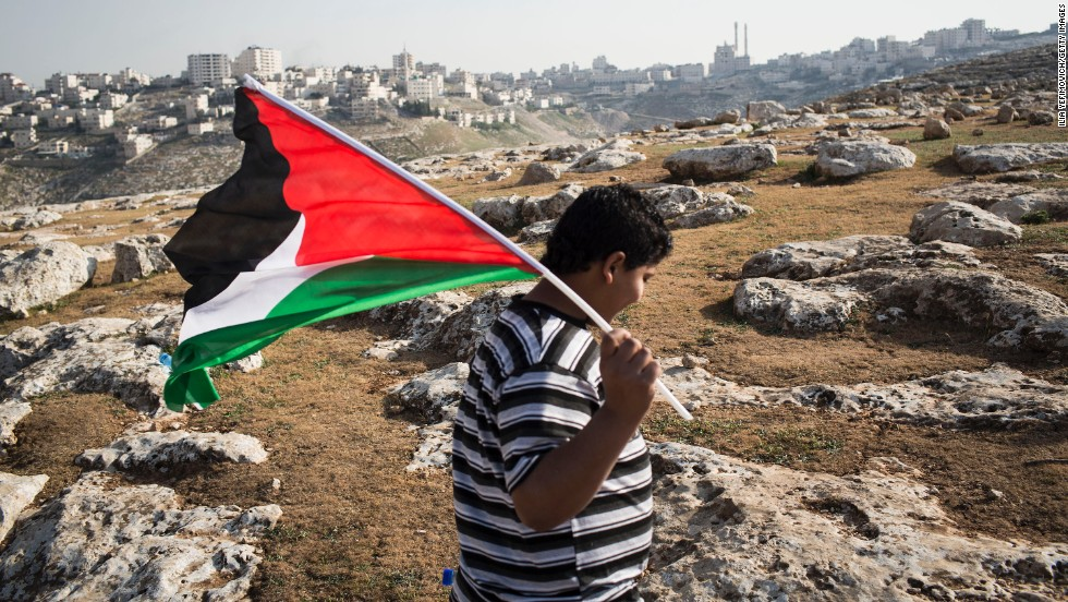 A boy waves a Palestinian flag at a camp Palestinians set up to demonstrate against Obama's visit on March 20.  Activists erected the tent city outside Jerusalem in the West Bank to protest the Obama trip and continued Israeli construction of settlements in what they consider an occupied territory.