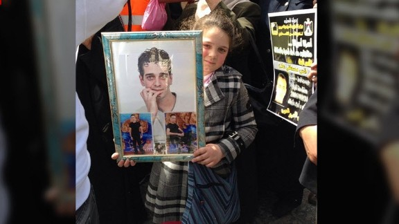 In the West Bank, a girl holds images of a loved one at a protest demanding the release of Palestinians detained in Israel.