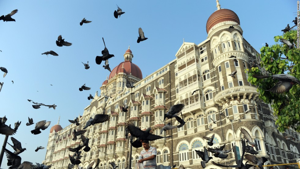 A man feeds pigeons outside the Taj Mahal Palace hotel in Mumbai, where luxury residential real estate averages £640 per square foot ($968).