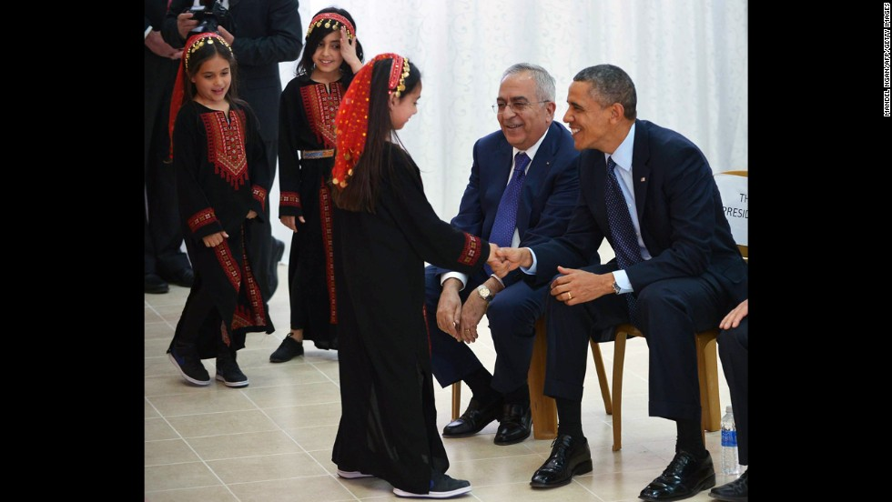 Obama and Salam Fayyad, prime minister of the Palestinian Authority, greet a young dancer following a performance at the al-Bireh Youth Center in Ramallah on March 21.
