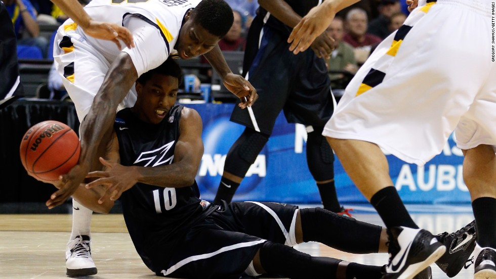Nick Harney of Akron looks to pass the ball from the ground against Jarred Guest of VCU on March 21.