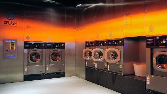 """What do you get when you cross being fresh with even fresher?  A laundromat that looks like a club! Splash, a chain of self-service laundromats in Spain, are a far cry from your average dingy neighborhood washhouse. According to designer Frederic Perers, the eco-friendly cleaning center features steel surfaces that reflect orange tones on the opposite wall, serving as a """"warm counterelement to the coldness of the metal."""" But will a club-like atmosphere really attract a younger clientele?"""