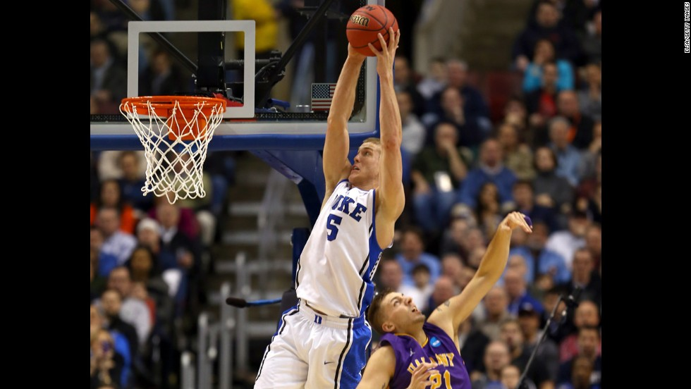 Mason Plumlee of the Duke Blue Devils, left, catches a pass for a dunk over Blake Metcalf of the Albany Great Danes on March 22.