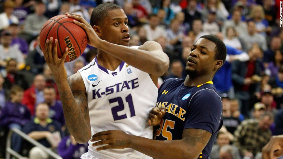 Jordan Henriquez of the Kansas State Wildcats, left, looks to pass against Jerrell Wright of the La Salle Explorers on March 22.