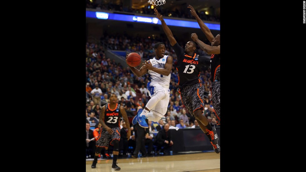 Austin Chatman of the Creighton Bluejays, center, looks to pass against Cheikh Mbodj of the Cincinnati Bearcats on March 22.