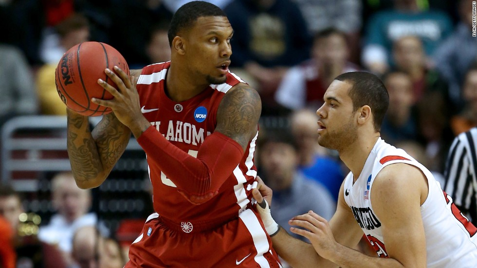 Cameron Clark of the Oklahoma Sooners, left, looks to pass against JJ O'Brien of the San Diego State Aztecs on March 22.