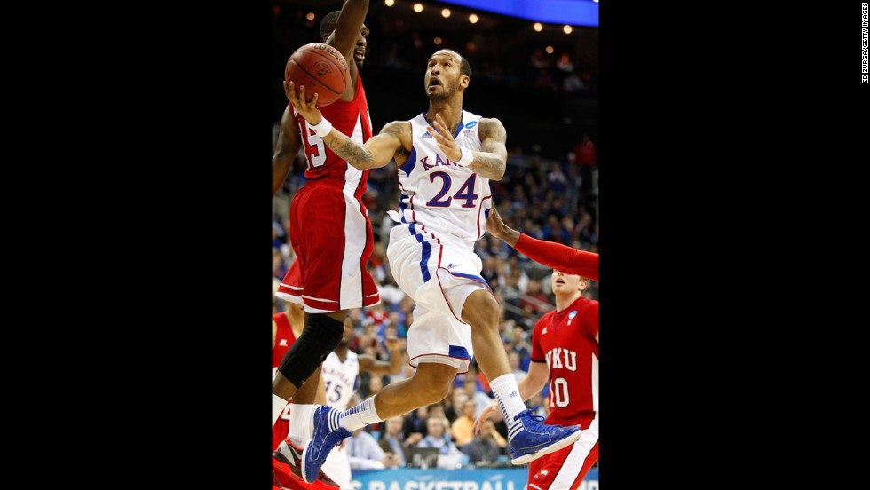 Travis Releford of the Kansas Jayhawks, center, shoots against O'Karo Akamune, left, and Caden Dickerson of the Western Kentucky Hilltoppers on March 22.
