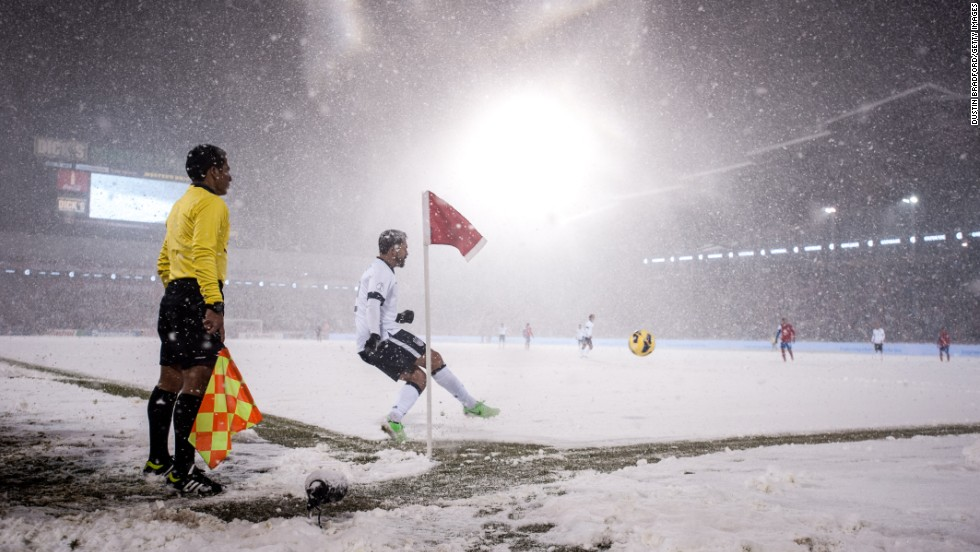 Forward Herculez Gomez of the United States sends a corner kick toward the goal as snow falls.