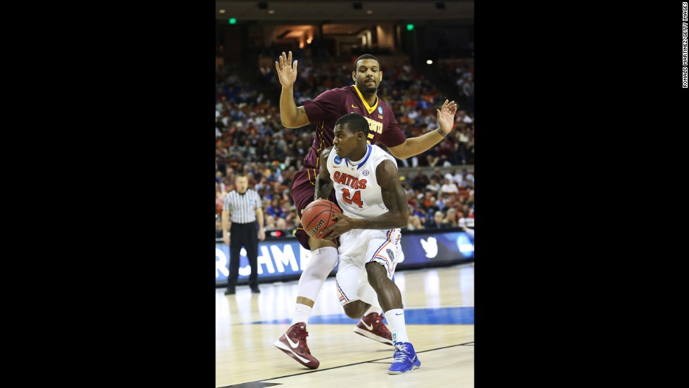 Casey Prather of Florida drives past Maurice Walker of Minnesota on March 24.