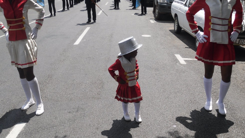 A young girl in uniform joins in the procession.