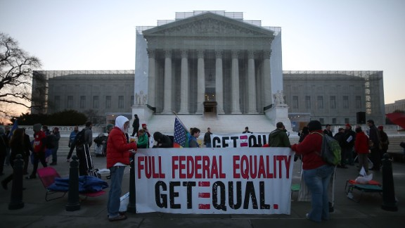 Banners are held up as people gather outside the Supreme Court on Tuesday.