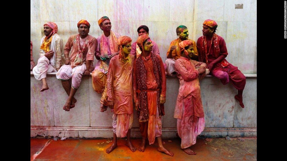 Men covered with colored powder and water stand inside a temple in Nandgaon, India, on March 22.