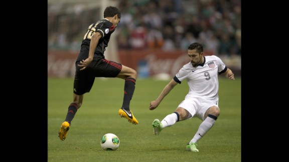 Mexican defender Diego Reyes vies for the ball with Hercules Gomez.