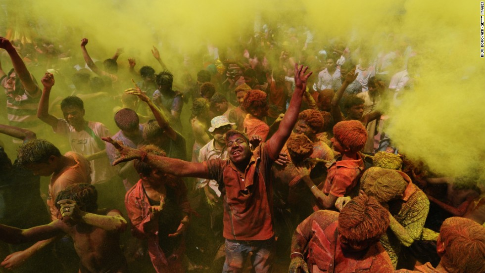 Revelers cover each other with colored powder during Holi celebrations in Guwahati, India, on March 27.