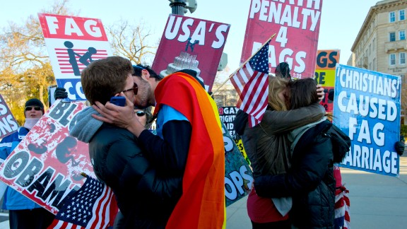 Same-sex couples kiss in front of protesters at the Supreme Court on Wednesday.